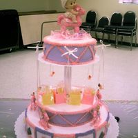 Pink Rocking Horse Carousel 3 tier baby shower cake. Top layer has babies swinging, middle layer is setting on top of the bottom layer. Bottom layer has rocking horses...
