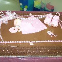 Baby In Pink Full sheet cake iced with brown buttercream icing. (no chocolate) Baby blanket made out of fondont icing. Topped with baby rattle, bottle,...