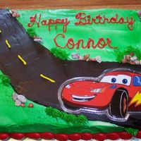 "Connor's Cars Cake  Done for my friends son, jello cake w/buttercream icing. CAR is actually taken from a t-shirt and mounted on ""Press and Seal""..."