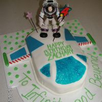 Buzz Lightyear This was made from a double layer 9 x 13 cake, cut to the shape of the space ship from Toy Story. Covered in white fondant; fondant wings,...