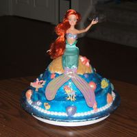 "Little Mermaid Cake 12"" round topped with original wonder pan, frosted in buttercream. Used glitter gel for water. Molded chocolate shells covered with..."