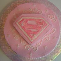 "Supergirl Cake   12"" round and 8"" square set on diagonal with one corner cut off. Iced w/buttercream and covered in pearl luster dust."