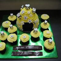 Bumble Bee Hive Cake My daughters 2nd birthday cake. She loves bees. Bees and flowers made by fondant. BC icing on beehive and cupcakes. Chocolate banner...