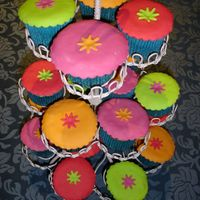 Exotic Cupcakes Late night treat, chocolate fudge cupcakes decorated in brightly coloured fondant, daisy cutouts.