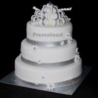 White With Silver Wedding Cake Covered with fondant, and decorations (bow, band and flowers) also made of fondant with lustre dust.