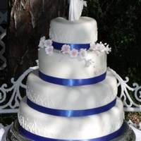 Summer Wedding 4 tier (6, 9,12, and 14 inch) WASC cake with buttercream icing and MMF. I free handed the piping with royal icing and the flowers are white...