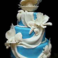 By The Sea   Dummy cake..wanted to try my hand at a beach theme cake. Hibiscus, shells, etc., gumpaste; coral is royal icing.