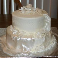 Small White Wedding Cake Frosted in buttercream fondant flowers and drapes painted with pearl dust.