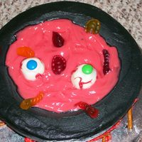 "Cauldron Cake Cake is devil's food with bc frosting. The ""blood"" is red colored white chocolate pudding. Cake ball eyes, pretzel wood, and..."