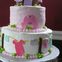 Baby In A Basket tiered baby shower cake with clothes line on sides of cake. Baby in a basket with clothes on top.