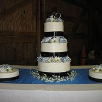 My First Wedding Cake Three tier stacked cake with two satellite cakes...Colors were white black and royal blue...