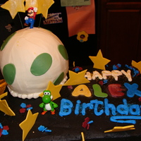 Super Mario Galaxy Butter cake with buttercream icing and fondant accents. Mario and Yoshi are toys.
