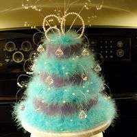 Feather And Jewel Cake 3 tier ( 4, 6 & 8) covered in purple fondant. decorated with teal feathers and jewels. Peanut butter cake with fudge filling
