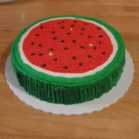 Watermelon Slice Single layer 10-inch round dark chocolate fudge cake with a layer of chocolate bravarian creme and frosted with almond buttercream. Seeds...