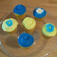 Blue And Yellow Cupcakes Yellow Cake cupcakes with vanilla buttercream. Royal icing flowers.