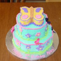 First Birthday This was a cake for a one year old with a flower and butterfly theme. The cakes were covered with buttercream with Fondant flowers. The...
