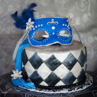Mask In Blue This was a chcolate and chi cake torted with lemon honey bc covered in mmf. I made the mask out of gum paste as well as the flowers. TFL. I...