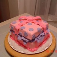 "Pink Giftbox Cake This is a 3 layer 7"" square cake in all buttercream with MMF accents. The bottom of the box is 2 layers of DH Devil's Food cake..."