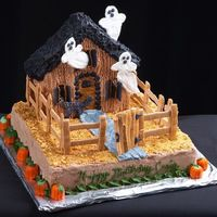 Haunted House   Chocolate cake with chocolate buttercream icing, the fence, ghosts , cat and shingles are royal icing.