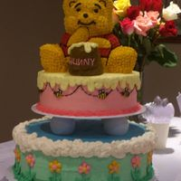 Winnie The Pooh This was my first tiered cake. Had a blast making it! It's yellow cake with BC icing. Used the Wilton stand up bear pan for Pooh and...