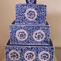 Blue Squares 3 tier wedding cake (dummy) Covered in fondant and air brushed blue. Piped royal conrelli lace with fondant blue and white flowers.