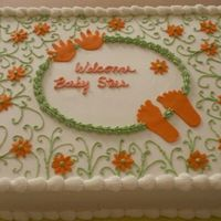 Baby Shower For Steer Double layer half sheet cake. Iced in buttercream with green scrolls and orange fondant daisy's feet and hands.