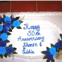 Blue Roses Anniversary Cake white cake with buttercream frosting with buttercream roses and gold foil leafs