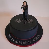 "Ozzy Osbourne Cake   9"" chocolate cake, cake covered in black sugarpaste (fondant). The figure is made from modelling paste."