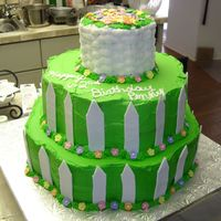 """garden""cake   three tier buttercream with fondant picket fence and fondant flowers. basket weave on top"