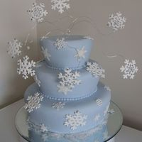 Blue Snowflake Cake Covered baby blue sugarpaste. Placed on table mirror rather than a cake board.Shaped cakes. Pastillage snowflakes.Snowflakes on wires made...