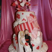 Topsy 2 Three tier topsy cake with sugar flowers and bows.Bride and Groom [soldier]