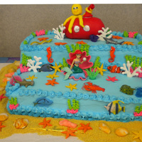 Under The Sea  Cake I made for my 3 daughters BD. Shells, starfish, submarine, octopus are fondant. The fish are plastic figures. Coral is royal icing....