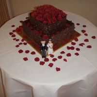 Chocolate Wedding Cake Yummy 2 tier choc mud cake iced with ganache with a solid chocolate embossed wrap around both tiers, roses and petals I made from gumpaste...