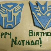 Transformers Birthday Cake Transformer masks made out of buttercream frosting, the letters made out of melted chocolate.