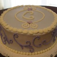 Monogram Cake A monogram cake for a going-away party for a co-worker. Usedscroll press along the sides. Royal icing violets on top. Tip 2 beads.