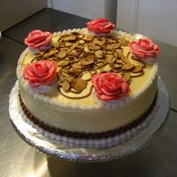 Almond Slice Cake Yellow buttercream base. Roses done with bag-striping.Almond slices scattered over top.