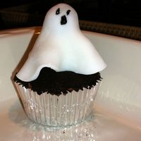 Ghost Cupcake   Halloween cupcake, yellow cake with chocolate icing. Oreo's for dirt. Ghost made from dum dum lollipop covered in fondant.