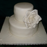 Ivory With Pearls And Large Rose Simple ivory with pearls and large rose. Amaretto with buttercream covered in chocolate fondant.