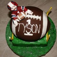 Football Baby this is a 1st birthday cake for the son of a football fan. The baby figurine was hand formed, and the cakes were carved. It was fun to make...
