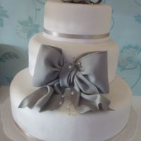 Contemporary Simple Wedding Cake Customer wanted a simple cake, but one that made a statement. Bow at front & on top modelled freehand and finished with sprays of...