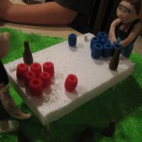Beer Pong Table Fondant people &cups . styro table top. marble cake with bettercream frosting topped with green sugar for grass. Thanks for looking!