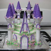 Enchanted Castle Yellow cakes with choc pudding filling..grandchildrens fav.Bc frosting and flowers. purple sugar for peaks on castle.