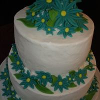 Two Tier Round With Turquoise Daisies Buttercream icing with fondant daisies...didn't like the color, but bride wanted it to match her theme