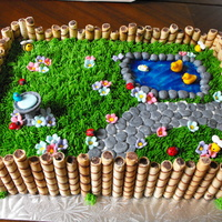 Spring Garden Buttercream grass, fondant decorations, piping gel pond, cookie fence. I have a lot of fun making this for a special 1 year old!