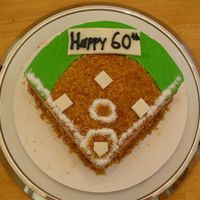 "Softball Cake  8"" round with sides cut away to form field. This was a sugar free chocolate frosting and it turned out pretty thin. I was in a rush to..."