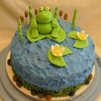 Frog And Lilypad Cake Buttercream icing for water and grass around bottom. Rocks, cattails, and flowers are gumpaste. Frog and lilypads are a mixture of MMF and...