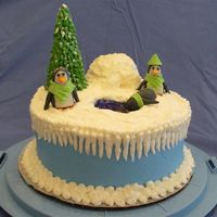 "Winter Penguins 8"" round two-layer with buttercream icing. Penguins are made out of gumpaste. Tree is ice cream cone with green icing piped on with..."