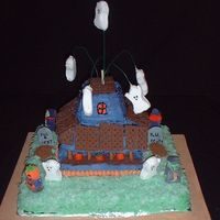 3-D Haunted House A haunted house with monsters in the graveyard and flying ghosts. This was carved from several sheet cakes. The shingles are graham...