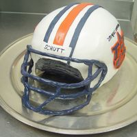 "Auburn University Helmet 3 10"" Chocolate cakes and a 9"" chocolate cake stacked with buttercream and carved into a round shape. The outside is covered in..."