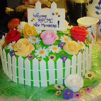 Spring Cake With Flowers And Picket Fence This was for a mothers' club tea. It was the first time I made flowers. The sign and fence pickets were fondant, as were the flowers....